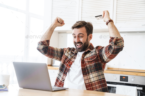 Portrait of excited man holding credit card and making winner gesture - Stock Photo - Images