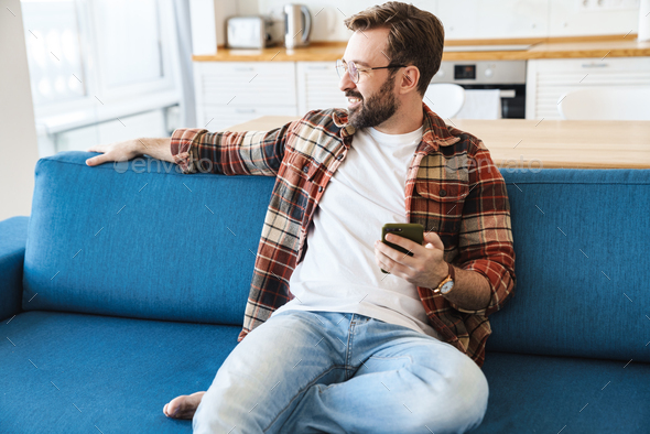 Portrait of young man smiling and using cellphone on sofa at home - Stock Photo - Images