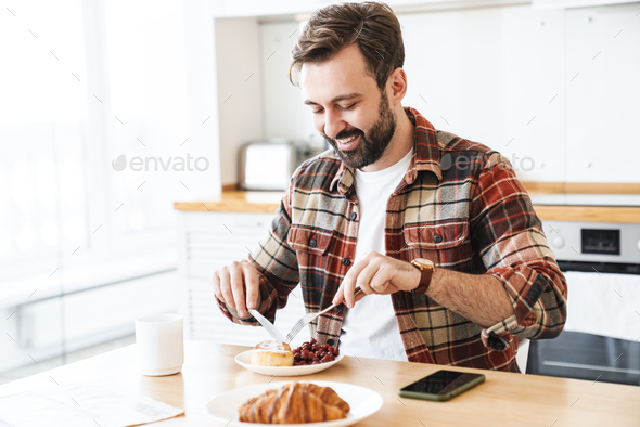 Portrait of joyful man smiling and eating cake while having breakfast - Stock Photo - Images