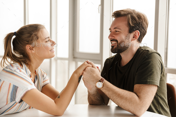 Photo of happy couple holding hands together and smiling while sitting - Stock Photo - Images