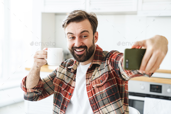 Portrait of smiling man taking selfie on cellphone and drinking coffee - Stock Photo - Images