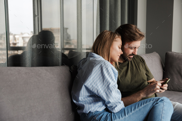 Photo of pleased beautiful couple hugging and using mobile phone - Stock Photo - Images
