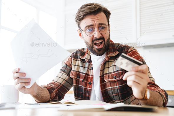 Portrait of shocked man holding credit card and papers while working - Stock Photo - Images