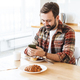 Portrait of cheerful man using cellphone while having breakfast - PhotoDune Item for Sale