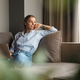 Image of woman using laptop and looking aside while sitting on sofa - PhotoDune Item for Sale