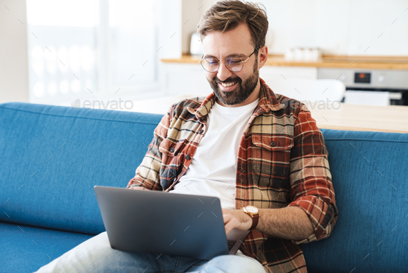 Portrait of young happy man smiling and using laptop on sofa at home - Stock Photo - Images