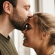 Photo of romantic cute couple smiling and kissing while standing - PhotoDune Item for Sale