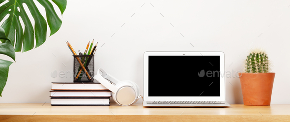 Stylish home studio workspace with laptop, supplies and headphones - Stock Photo - Images