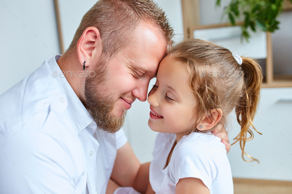 Adorable little girl in white dress hugging loving father - Stock Photo - Images