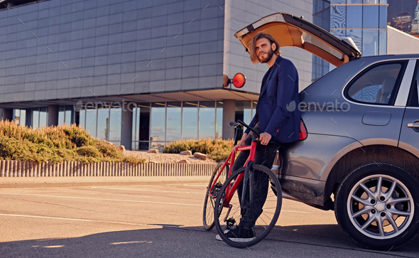 A man holds fixed bicycle near the car with open trunk. - Stock Photo - Images