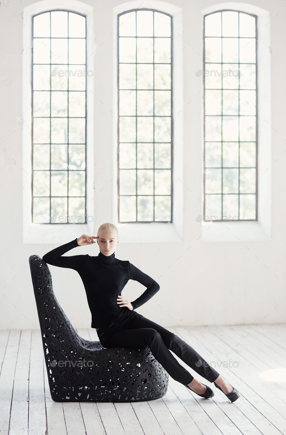 Female in a black costume sits on a round black. - Stock Photo - Images