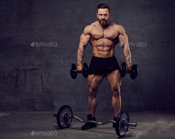 Muscular, bearded male doing biceps workouts with dumbbells. - Stock Photo - Images