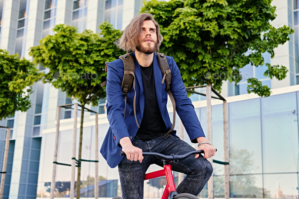 A man with backpack sits on the red fixed bicycle. - Stock Photo - Images