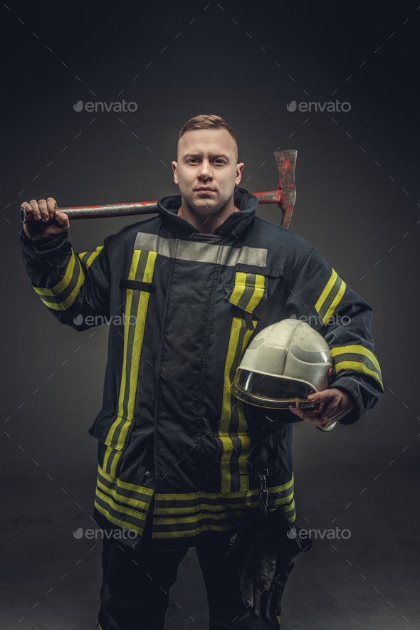 Firefighter costume holding helmet and recue red axe. - Stock Photo - Images