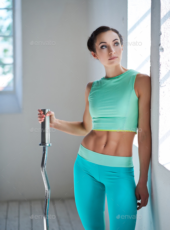 Female in azure sportswear holding berbell. - Stock Photo - Images