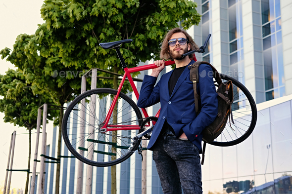 A man holds red single speed bicycle on his shoulder. - Stock Photo - Images