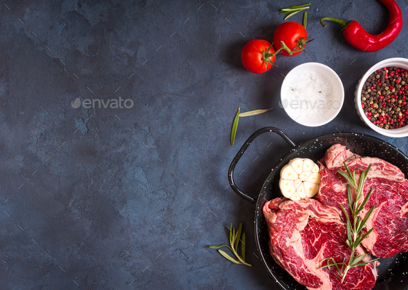 Raw meat steak on rustic concrete background ready to roasting - Stock Photo - Images