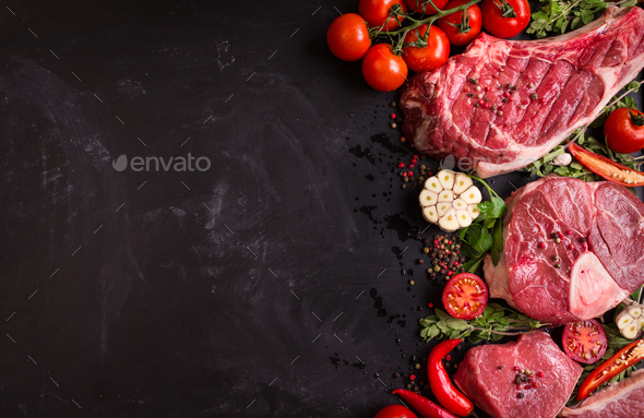 Raw meat steaks on a dark background ready to roasting - Stock Photo - Images