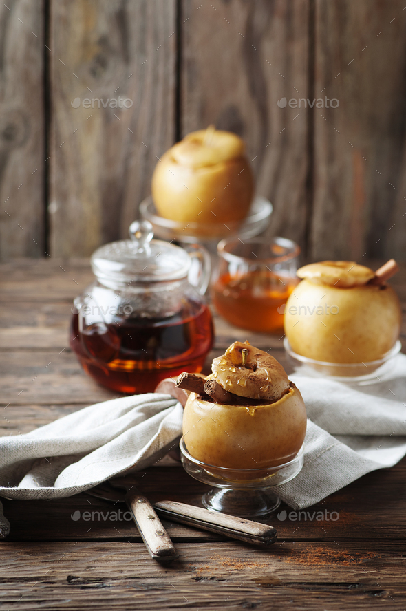 Baked apples with honey and cinnamon on the wooden table - Stock Photo - Images