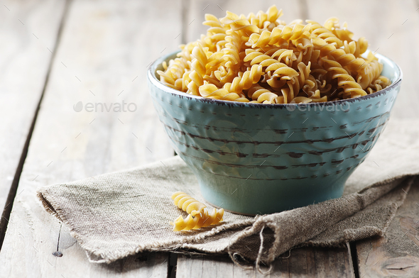 Integral raw pasta fusilli on the table - Stock Photo - Images