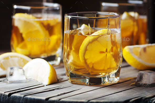 Cold whiskey with ice and lemon on the vintage table - Stock Photo - Images