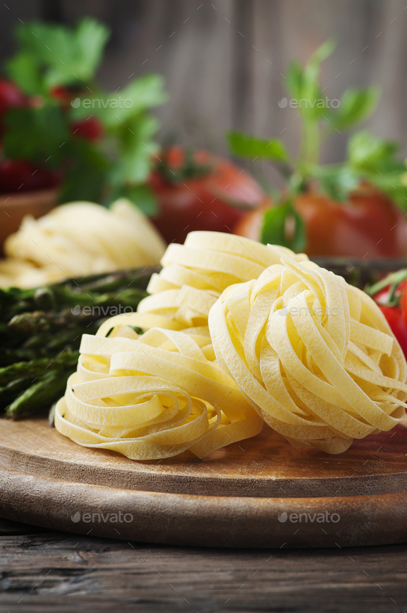 Italian homemade pasta with raw asparagus - Stock Photo - Images