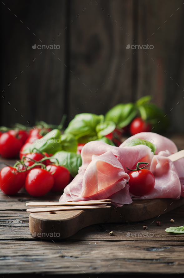 Italian traditional prosciutto with tomato and basil on the wooden table - Stock Photo - Images