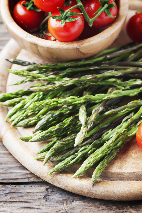 Uncooked asparagus with tomato on the vintage table - Stock Photo - Images