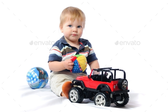 Toddler plays with loved toy holding plush ball - Stock Photo - Images