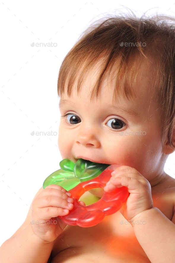 Little baby holds on hand teether, Baby bites teething toy - Stock Photo - Images