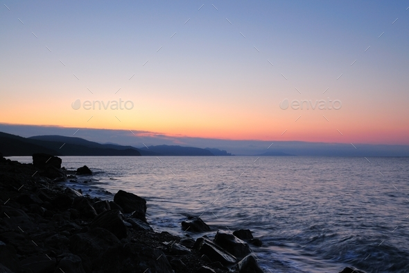 Sunset by the sea, beach strewn with stones - Stock Photo - Images