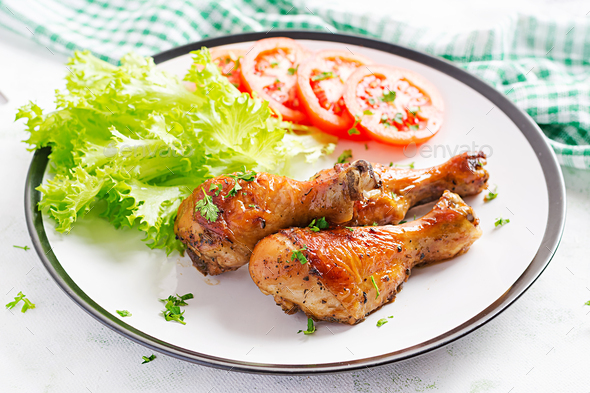 Grilled chicken legs with spices and fresh vegetables. Baked drumsticks. - Stock Photo - Images