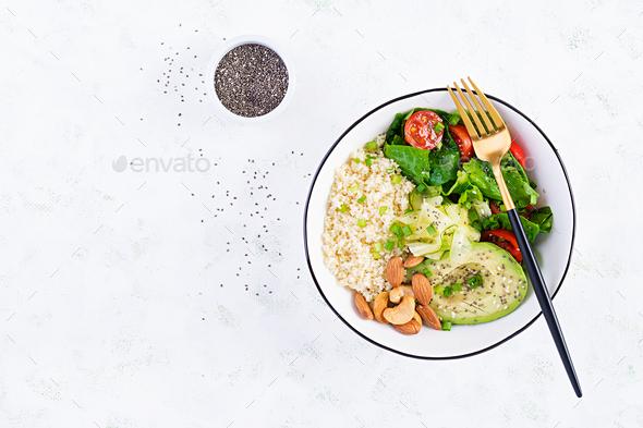 Vegan Buddha bowl with bulgur, avocado, cucumber, lettuce, tomatoes and chia seeds - Stock Photo - Images
