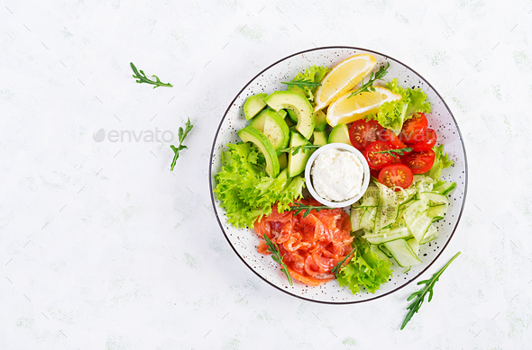 Salad of salted fish salmon, avocado, cherry tomatoes, cucumber, lettuce and cream cheese. - Stock Photo - Images
