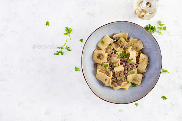 Pasta Calamarata with minced meat in blue bowl. Italian cuisine. Top view, overhead - Stock Photo - Images
