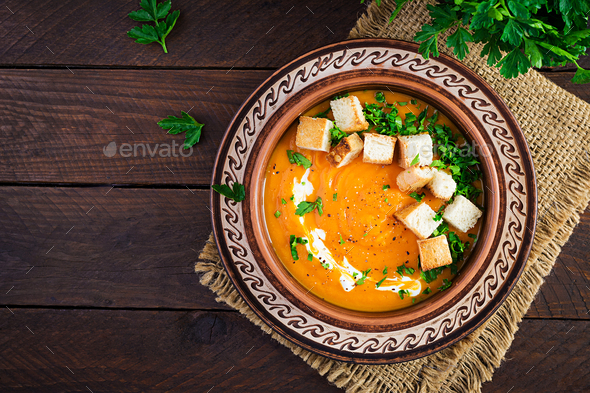 Pumpkin soup in a bowl served with croutons and parsley. Vegan diet soup. - Stock Photo - Images