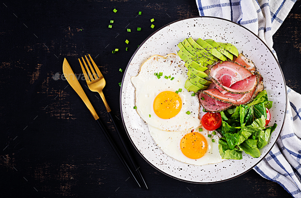 Ketogenic/paleo diet. Fried eggs, ham, avocado and fresh salad. - Stock Photo - Images