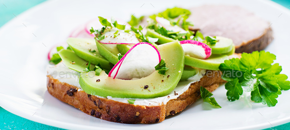 Tasty breakfast. Healthy avocado toast and radish on whole grain bread and baked sliced meat. - Stock Photo - Images