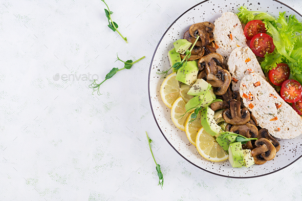Chicken meatloaf, fried mushrooms with salad fresh tomatoes and avocado. - Stock Photo - Images