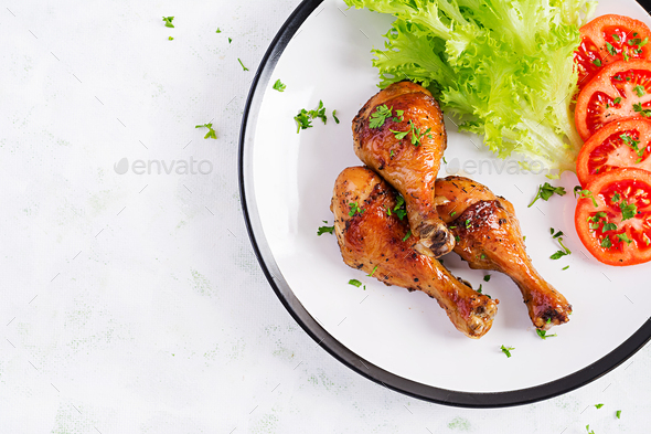 Grilled chicken legs with spices and fresh vegetables. Baked drumsticks. Top view, flat lay - Stock Photo - Images
