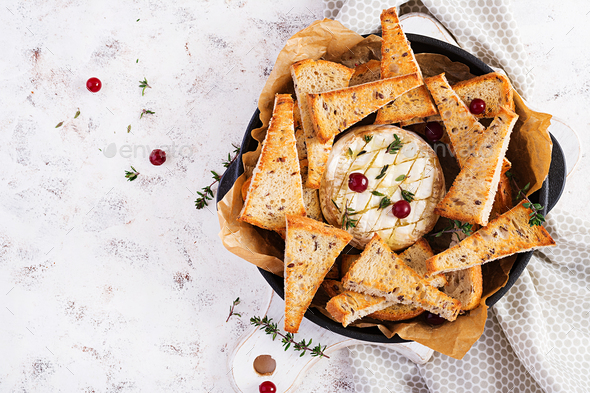 Baked camembert with toasts and thyme on light  background. Top view, overhead - Stock Photo - Images