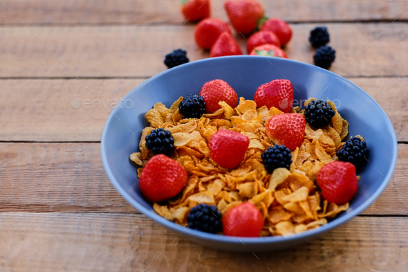 Corn flakes on a strawberry and blackberry on a plate. - Stock Photo - Images