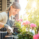 Beautiful woman among flowers at her balcony during planting - PhotoDune Item for Sale