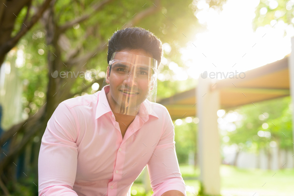Happy young handsome Indian businessman with face shield smiling at the park - Stock Photo - Images