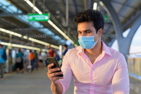 Young Indian businessman wearing mask and sitting with distance while using phone at the skytrain - Stock Photo - Images
