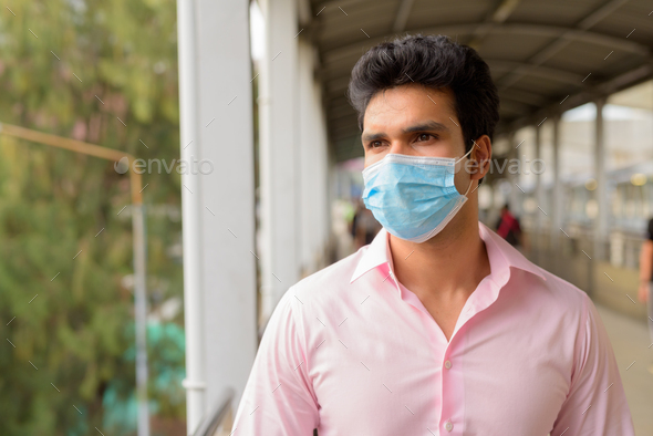 Face of young Indian businessman with mask thinking at the footbridge - Stock Photo - Images