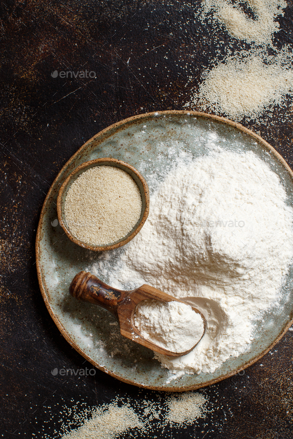 Raw fonio flour and seeds with a spoon on a plate on dark background - Stock Photo - Images