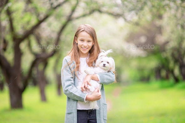 Little smiling girls playing and hugging puppy in the park - Stock Photo - Images