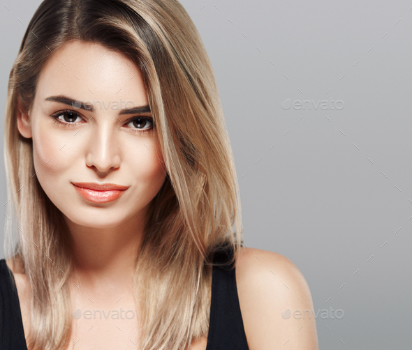 Beautiful young woman portrait smiling posing attractive blond gray background - Stock Photo - Images