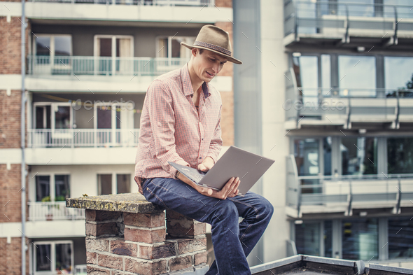 Man in hat with laptop. - Stock Photo - Images